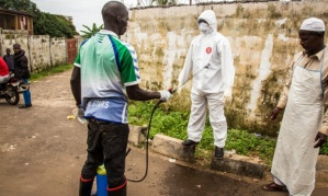 A health worker is disinfected after assisting with a suspected case of Ebola in Freetown, Sierra Leone. Photograph: Michael Duff/AP