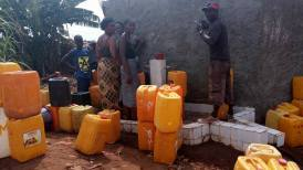 Residents of Grass Field community queuing for water at a WASH tap