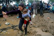 Syrian refugee cries as she carries her baby through mud after crossing border from Greece into Macedonia