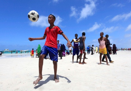 Somali boys play football in Lido beach while celebrating the Muslim Eid al-Fitr holiday, which marks the end of the fasting month of Ramadan, in capital Mogadishu