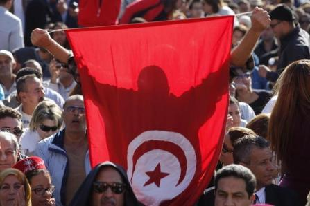 Supporter of Beji Caid Essebsi, Nidaa Tounes party leader and presidential candidate, holds a Tunisian flag during the opening of his campaign headquarters in Monastir