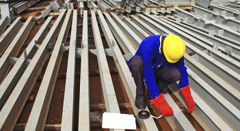 A construction worker takes measurements of roofing metal bars of a new hospital under construction in Hoima