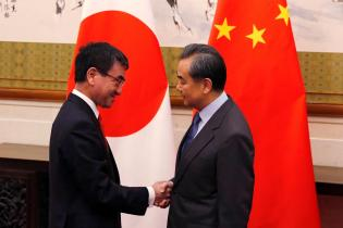 Japanese Foreign Minister Taro Kono shakes hands with his Chinese counterpart Wang Yi before their meeting at the Diaoyutai State Guesthouse in Beijing