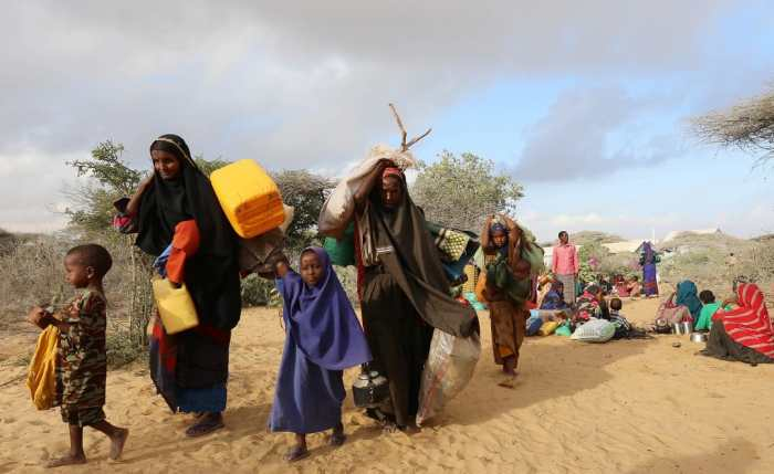 Internally displaced Somalis carry their belongings as they flee from drought stricken regions in Lower Shabelle region before entering makeshift camps in Somalia's capital Mogadishu