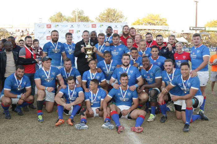 Namibia captain Johan Deysel and coach Phil Davies hold the Africa Gold Cup trophy, surrounded by th
